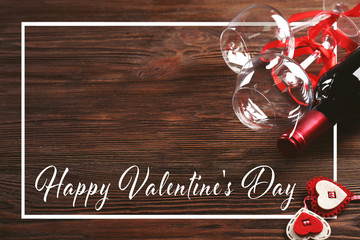 Text HAPPY VALENTINE'S DAY, glasses and bottle of wine on wooden background