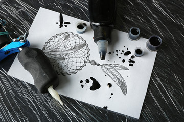 Tattoo machine, sketch and supplies on table