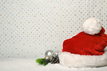 Santa Claus hat and Christmas decor on white shiny background
