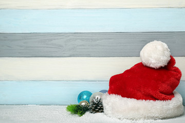Santa Claus hat and Christmas decor on colorful wooden background