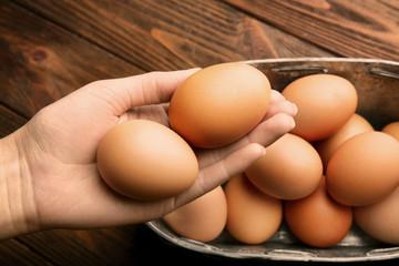 Female hand holding raw eggs, closeup