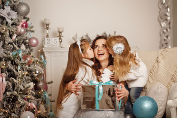 Daughters kissing mother and give her a Christmas present. Family celebration. Happy Motherhood and Childhood.