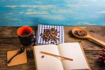 Roasted coffee beans, coffee, and notes on the wooden table. Taking note of the quality of the coffee beans is necessary.