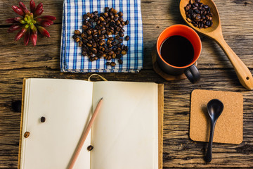 Top view, Roasted coffee beans, coffee, and notes on the wooden table. Taking note of the quality of the coffee beans is necessary.