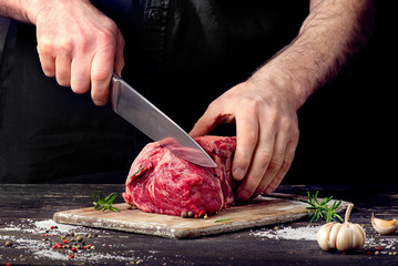 Photo sur Aluminium Viande Man cutting raw beef meat