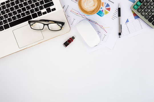 Modern White office desk table with laptop computer, eyeglasses, mouse, calculator,pen,analysis chart or graph and cup of coffee.Top view with copy space.Working desk table concept.