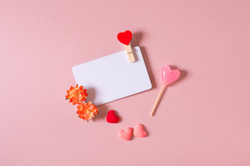 Valentine day composition: credit / visiting card template with clamp, spring flowers, candy and small hearts on light pink background. Top view.