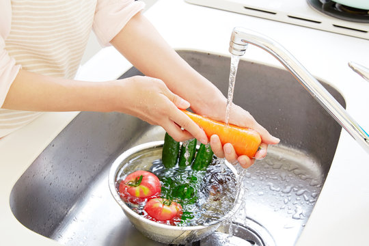 女性 野菜を洗う キッチン