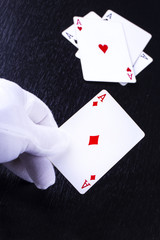 hand of the dealer in white gloves in a casino handing out card