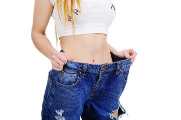 slim stomach girl in jeans large size on a white background. Weight Loss