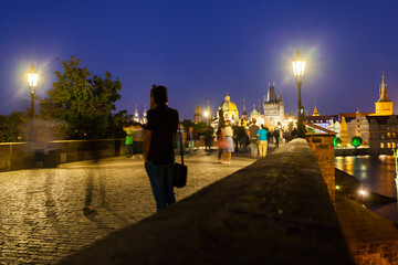 Prague, Czech Republic. Charles Bridge with its statuette at night, Old Town Bridge Tower in the background.