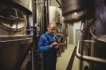 Owner using digital tablet at brewery