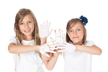 girls - sisters show painted white hands, palms. Fun, creativity, painting.