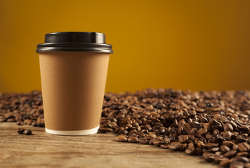 Paper cup of coffee on brown background