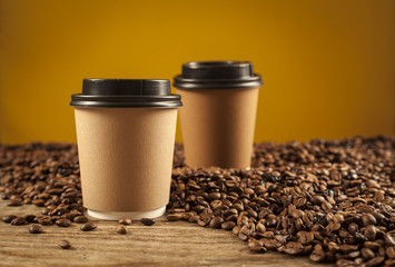 Paper cups of coffee on brown background
