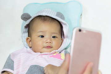 Cute new born baby looking mobile phone.