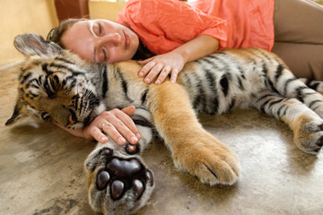 Young woman hugging baby tiger in Chiang Mai, Thailand