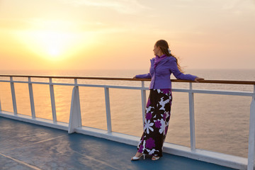 Portrait of young woman posing at sunset on a cruise ship. Looki