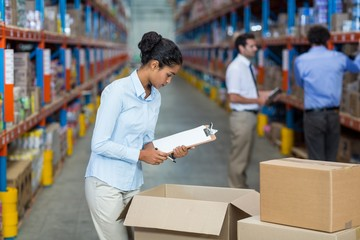 Female warehouse worker with a clipboard checking the boxes