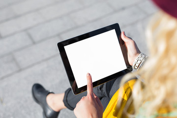 Person sitting outside and using blank screen tablet