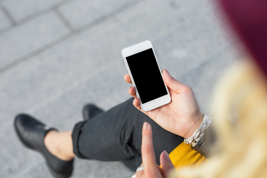Woman sitting outside and using smartphone