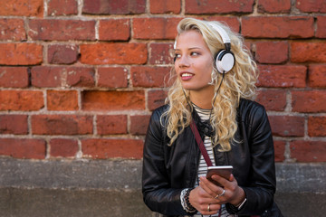 Modern woman listening to music on her smartphone