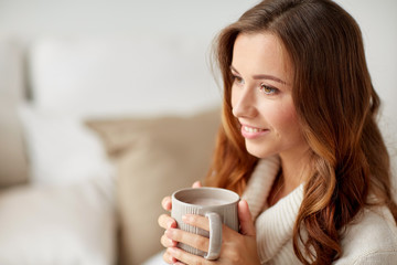 happy woman with cup of cocoa or coffee at home