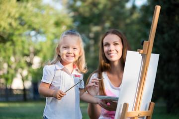 мама и дочка рисуют красками в парке