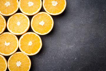 Fresh and juicy half cut oranges on dark stone table