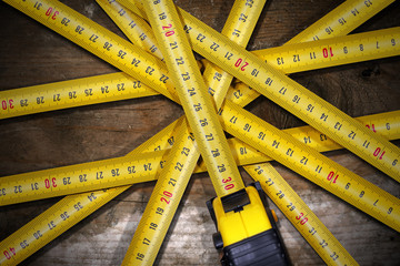 Group of Tape Measures on Wooden Table