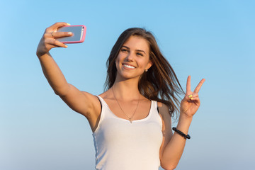 Brunette woman on summer vacation trip taking selfie photo with