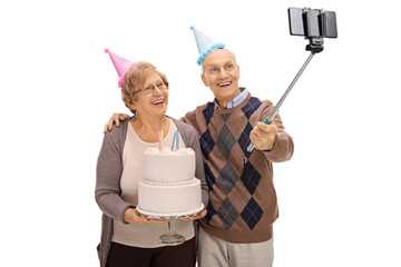 Joyful seniors with party hats and birthday cake taking a selfie