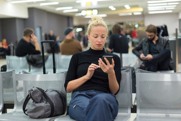Casual blond young woman using her mobile phone while waiting to board a plane at airport departure gates.