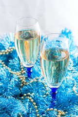 Two crystal wine glasses with champagne in Christmas decor, selective focus