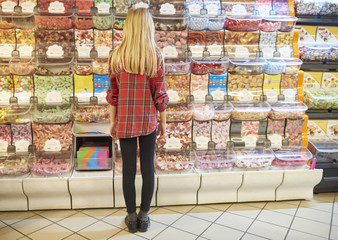 Rear view of blond girl picking candies
