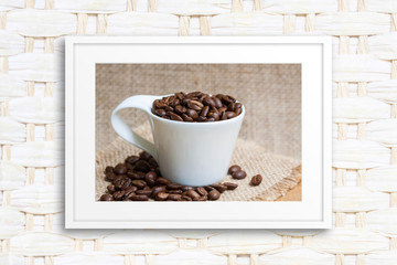 Interior decoration. Coffee motif picture in frame on rattan textured background.
