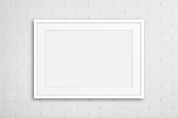 Blank photo frame on white bricks textured wall