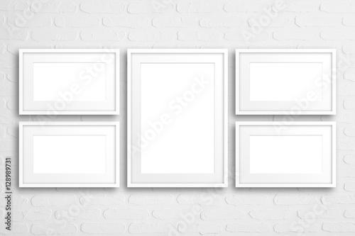 Blank frames collage on white bricks wall\
