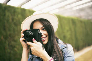 Young woman wearing hat taking picture with camera