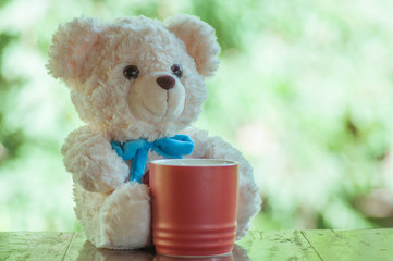 Teddy bear with red coffee cup on wooden table