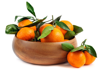 Fresh tangerines with green leaves in a wooden bowl