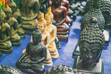 Various Thai Buddhist statuettes and souvenirs for sale at night market, Rambuttri Alley, Bangkok, Thailand. Soft focus