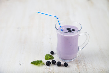 Smoothie or yogurt with blueberries on a wooden table. Delicious