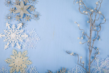 Silver decorative snowflakes and branch on a blue wooden backgro