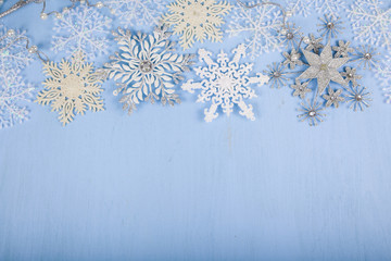 Silver decorative snowflakes on a blue wooden background. Christ