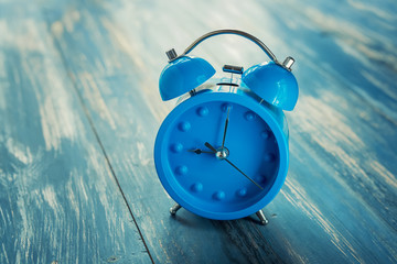 blue clock on antique rustic wood background.