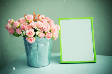 Still life of empty photo frame with rose. Vintage tone filtered