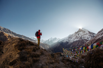 Tourist man watching and taking mobile photo of sunrise over the sacred mountain Machapuchare from Annapurna Base Camp in Himalaya Mountains