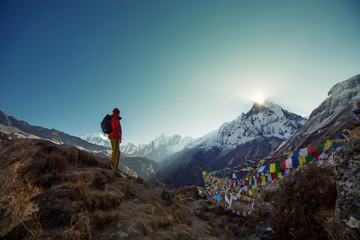 Tourist man watching sunrise over the sacred mountain Machapuchare from Annapurna Base Camp in Himalaya Mountains