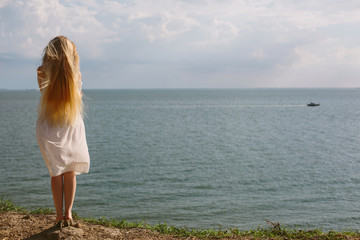 Young Blond woman in white dress enjoy summer outdoor on sea beach